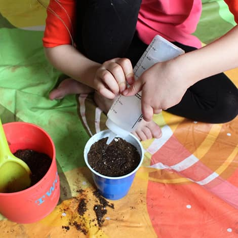 A child uses a squeeze bottle to water her mini greenhouse