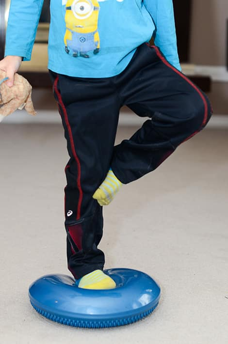 Standing on a balance cushion, a child tries to balance on one leg.