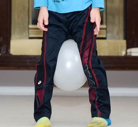 A child waddling with a balloon between his knees.
