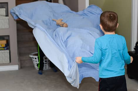 Two kids holding a bed sheet and tossing a stuffie with it.