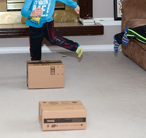 A child jumping over a series of cardboard boxes.