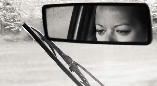 a mother looks guilty in her car mirror