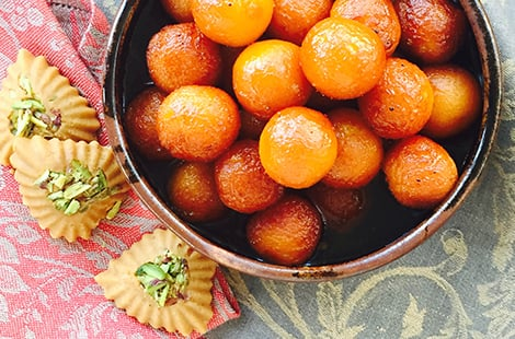 Bird's eye view of gulab jamon, which are sweet dough balls in syrup.