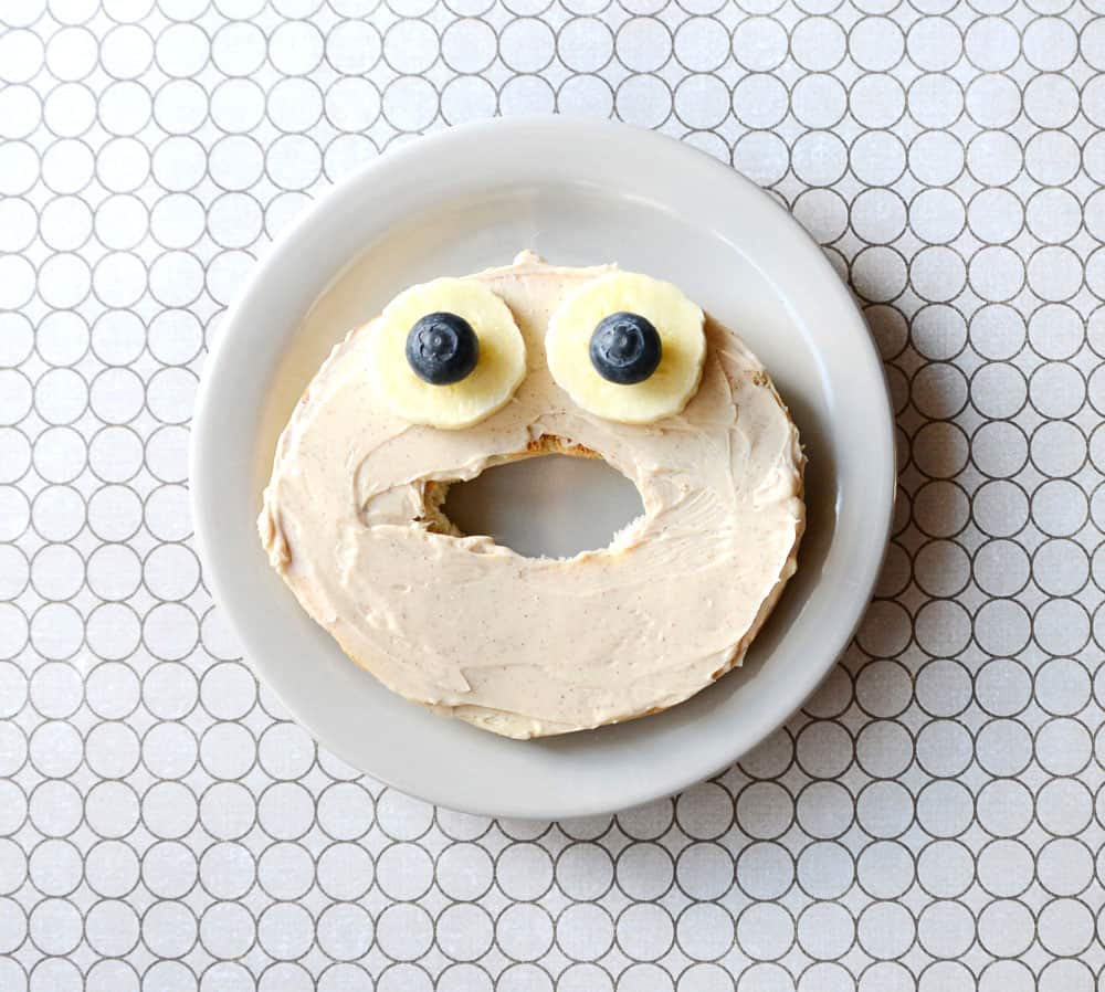 A bagel face with eyes made from bananas and blueberries.