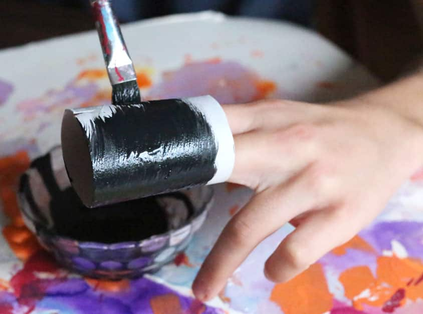 A child paints a cardboard tube with black paint.