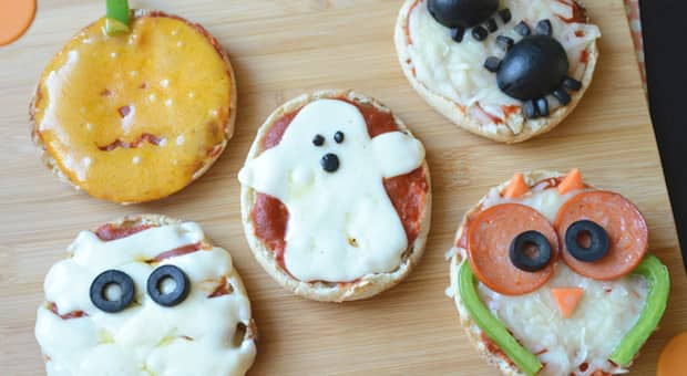 Five different halloween-themed english muffin mini pizzas sitting on a cutting board.