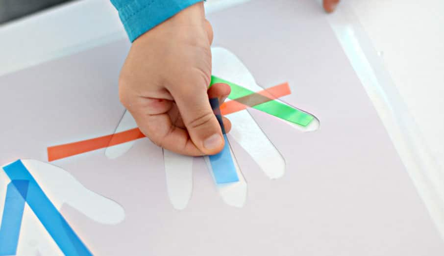 A small hand placing strips of coloured transparency paper onto the sticky part of a contact-paper handprint.