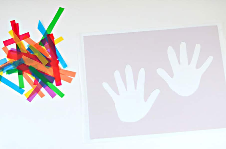 A pile of brightly coloured strips of coloured transparancies sitting next to a piece of cardstock with two small hand prints cut out of it.