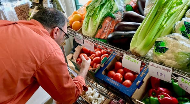 a dad shops the fresh produce section of a grocery store