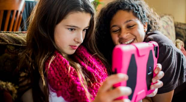 Young girls watch a video on an tablet