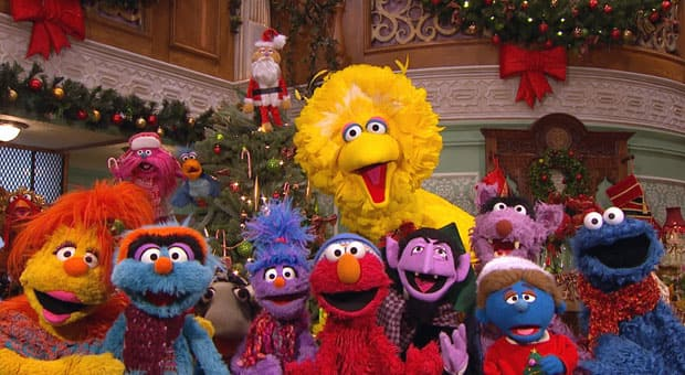 The gang from the Furchester Hotel, including Big Bird, Cookie Monster and Elmo, gather around a Christmas tree.