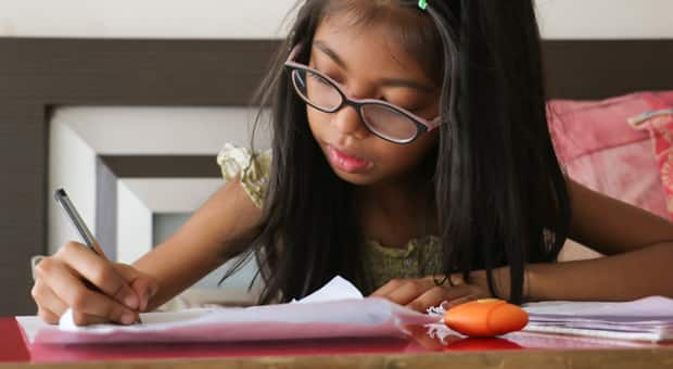 a young girl is doing her homework