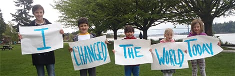 Kids hold signs that say: