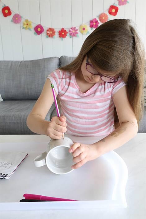 Young girl draws on mug with a pencil.