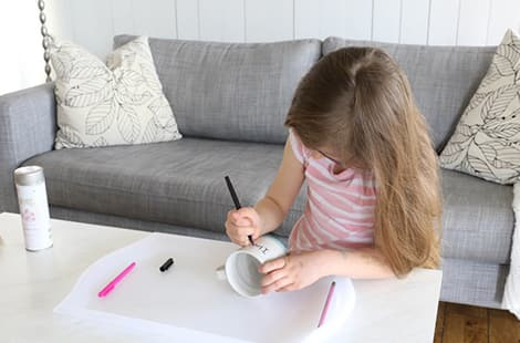 Little girl draws on mug with marker.