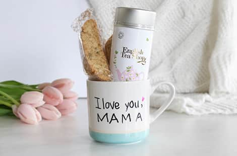 A personalized mug with a biscotti and tea tin inside.