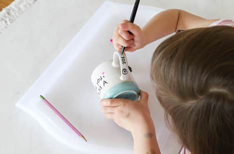 Child adds date on handle of teacup.