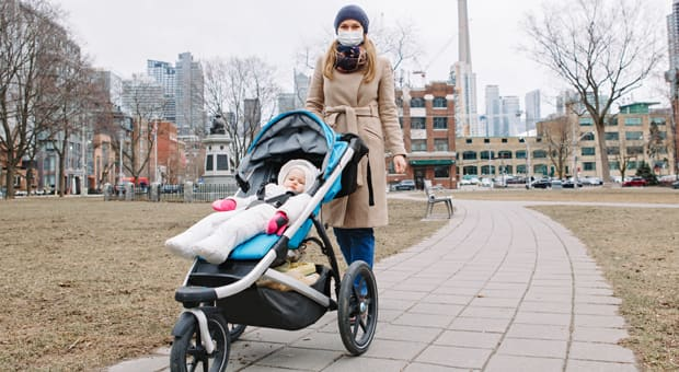 A mother wears a mask while walking her child through a park