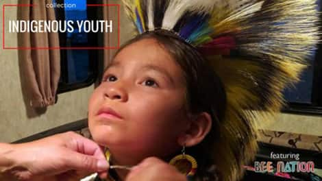 Child is wearing traditional Indigenous head feathers.