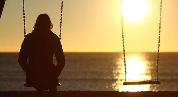Woman sits on swing, looking at the sunset