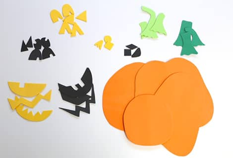 A variety of shapes cut out and ready for play: different pumpkin shapes, stem shapes, eye shapes, nose shapes and mouth shapes. There are about three of each kind of shape.