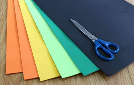 A pair of scissors sitting on top of the needed foam: two sheets of orange craft foam, one sheet of yellow craft foam, one sheet of black craft foam and two sheets of green craft foam (in two different shades of green).