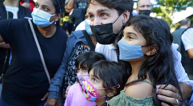 Justin Trudeau poses with kids wearing a mask during a tour stop during his election campaign