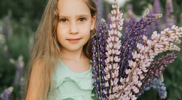 Young girl poses with an assortment of purple flowers