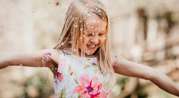 a young girl celebrates her birthday with a confetti shower