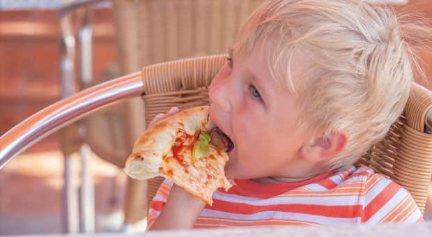 young kid eating pizza too fast