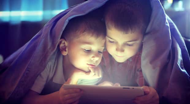 kids reading e-reader in bed