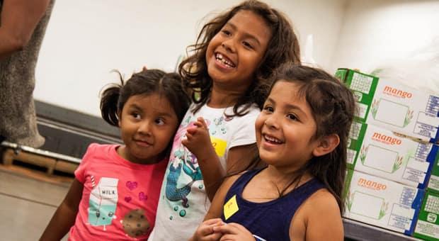 three young girls volunteering at a food bank