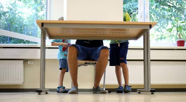 two young boys accompany their dad to vote in an election