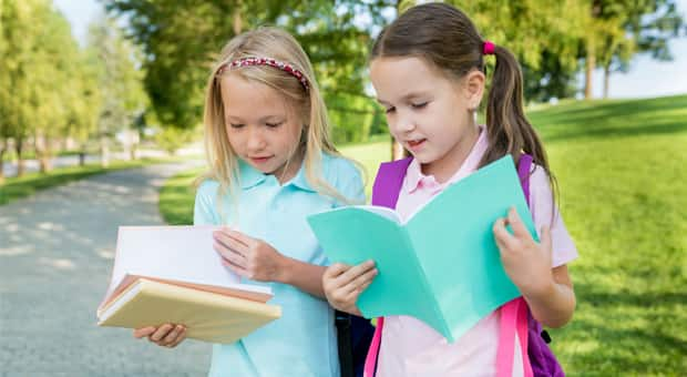 two young children with backpacks and school folders, trying to see what's inside