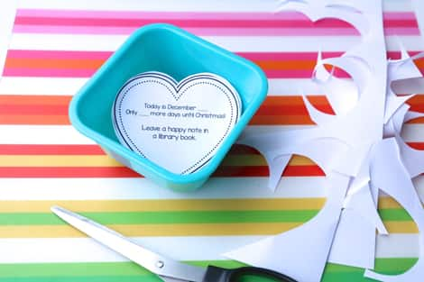 The kindness activities have been cut out and placed in a small dish. There are scraps of paper sitting on the table next to a pair of scissors.