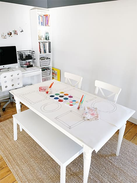 Place mats with hand-drawn picture frames on table accompanied by paints.
