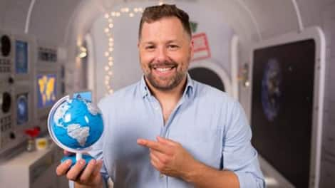 Bearded man points to a globe that he's holding.