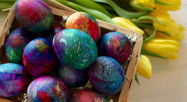 A basket of colourfully tie-dyed eggs on a basket beside yellow tulips
