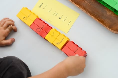 A child arranging the blocks in a line to create a musical combination