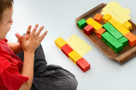 Little boy clapping out the rhythm arranged in front of him with Duplo blocks