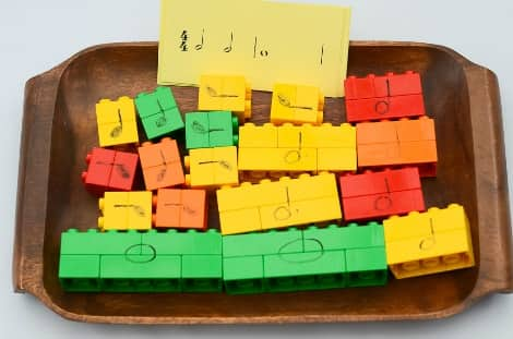 A wooden tray with the Duplo blocks arranged into different notes with their designated note written on the block in permanent marker