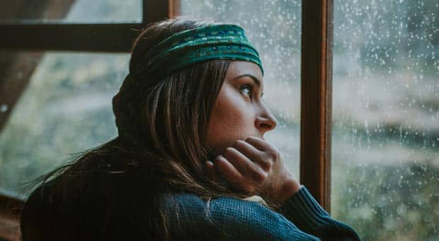 a woman looks pensively out a window and she's wearing a headband and chunky sweater with a raised eyebrow