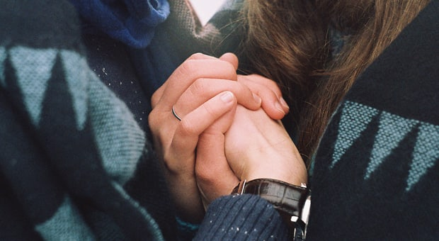 married couple warmly holding each other's hands