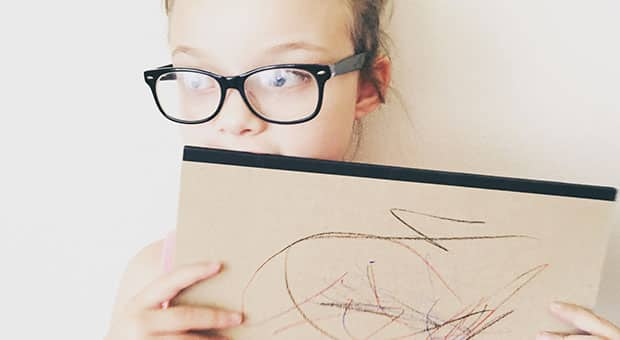 Young girl with glasses looks away from the camera while holding a sketch pad.