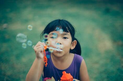 Little girl blows bubbles outside.