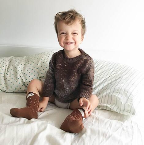 Child smiles at camera.