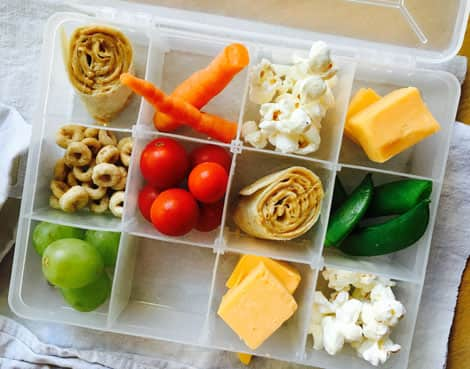 A small tackle-box style lunch filled with wraps, carrots, popcorn, dry cereal, tomatoes, grapes, cheese and shelled peas.