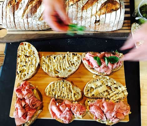A platter covered with slices of bread coated with mayonnaise, some with sliced meat and lettuce.