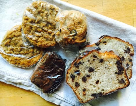 A pile of cookies, muffins and slices of loaf wrapped individually in plastic wrap.