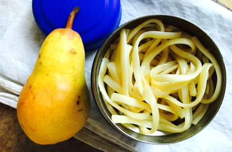 A a thermos full of cooked pasta sitting next to a pear.